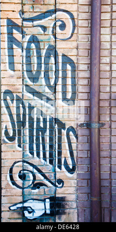 Painted sign on old brick wall for food and spirits - Stock Photo