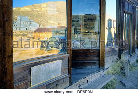 Shop front of Boone Store in gold mining ghost town of Bodie, northern California, USA, reflects vintage car and - Stock Photo