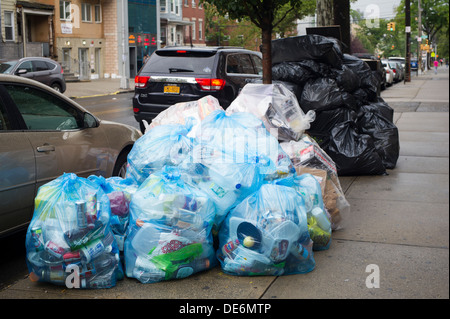 Piles of trash in plastic bags await pick-up curbside in Astoria in Queens in New York - Stock Photo