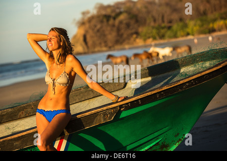 A young girl savors the warmth of the morning sun on a beach in Costa Rica. - Stock Photo