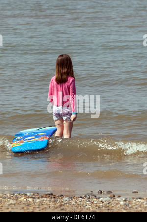 Young girl age 6-7 years on beach paddling in the sea, Mundesley Beach, Norfolk East Anglia UK - Stock Photo