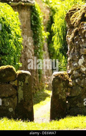 Old stone squeeze stile in drystone wall leading from pasture to Winster village, Peak District National Park, Derbyshire, - Stock Photo