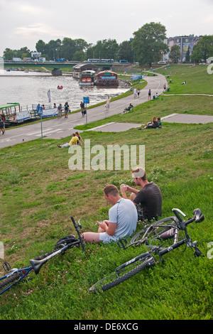 Krakow residents relaxing on bank of Vistula River. - Stock Photo