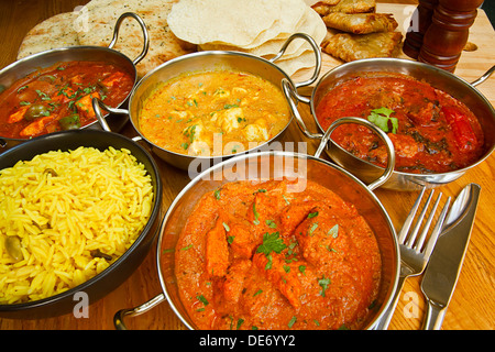 Varied selection of indian cuisine on table including Chicken Tikka, beef rogan josh, chicken jalfrezi and chicken - Stock Photo