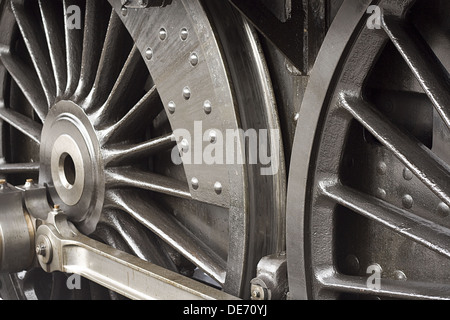 Steam train wheels close up detail shot of the chassis or running gear - Stock Photo