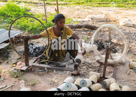 India, Uttar Pradesh, Agra,woman spinning cotton on basic machinery - Stock Photo