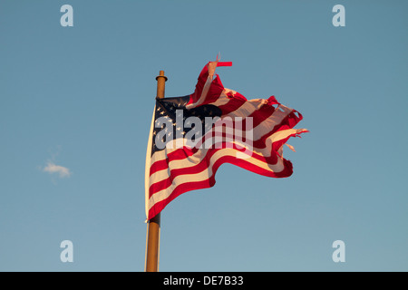 A old torn and tattered American flag flying on a flagpole - Stock Photo