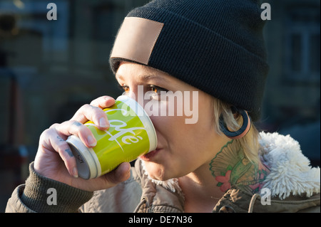 Germany, Freiburg, Young woman with tatoo drinking coffee, close up - Stock Photo
