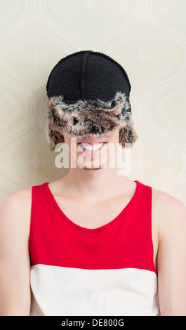 Lifestyle portrait of laughing young man with winter hat pulled down to cover his eyes - Stock Photo