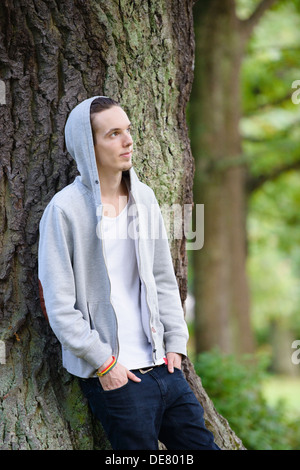 Young man standing by himself and thinking in a forest - Stock Photo