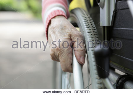 Germany, North Rhine Westphalia, Cologne, Senior woman sitting on wheelchair, close up - Stock Photo