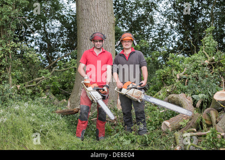 Tree surgeons holding chainsaws in woodlands. - Stock Photo
