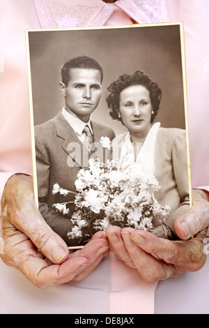 Old woman hands with antique portrait - Stock Photo