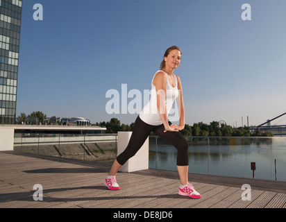 Germany, North Rhine Westphalia, Duesseldorf, Young woman stretching - Stock Photo