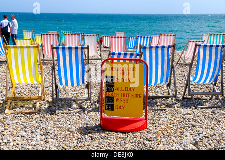 Deck chairs and hire sign on beach at Beer, Devon, England - Stock Photo