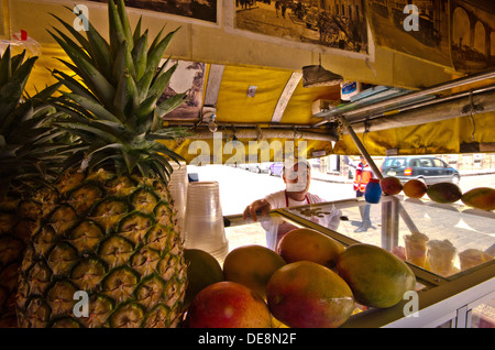 Street vendor selling fresh fruit from his mobile stall in Queretaro in Mexico - Stock Photo