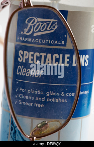 dirty pair of reading glasses with Boots pharmaceuticals Spectacle Lens Cleaner - Stock Photo
