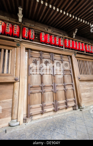 Grand wooden doorway and red lanterns on a traditional Japanese building - Stock Photo