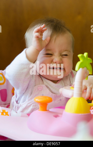 eight month old baby girl sitting in high chair with toys - Stock Photo