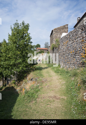 Pilgrims walking into the small French village of La Roche on the GR65 the Way of St James in France - Stock Photo