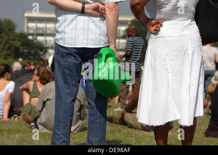 People watching live music at Lambeth festival at Brockwell Park, South London, England in 2013 - one carrying a - Stock Photo