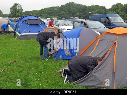 Happy campers erecting a tent at a festival or sporting event (F1 Grand Prix) - Stock Photo