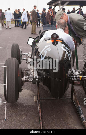 A vintage single seater racing car sits on jacks with the engine running and the rear wheels spinning in the paddock - Stock Photo