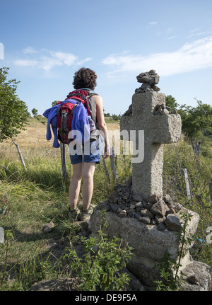 Pilgrim standing next to stone cross waymarker on the GR65 walking route the Way of St James in the Auvergne region - Stock Photo
