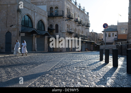Two nuns walking along cobbled street in morning light. Jerusalem Old City. Israel. - Stock Photo