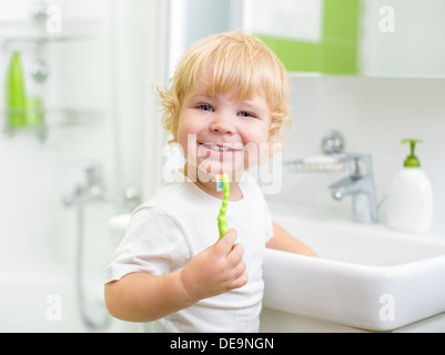 Happy kid or child brushing teeth in bathroom. Dental hygiene. - Stock Photo