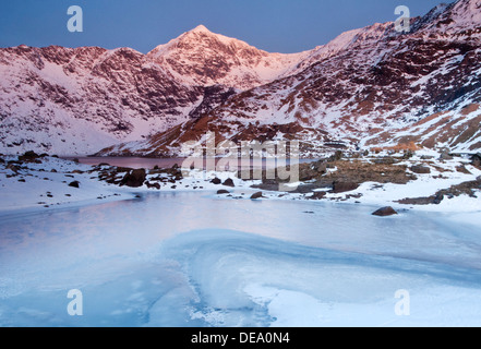 First Light on Mount Snowdon over Frozen Llyn Llydaw, Snowdonia National Park, North Wales, UK - Stock Photo