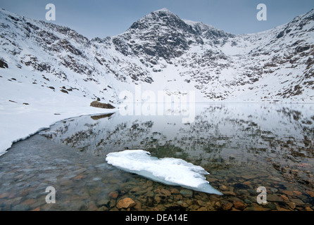 Ice Formations in Llyn Glaslyn and the Snow Capped Peak of Mount Snowdon, Snowdonia National Park, North Wales, UK