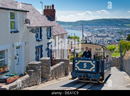 A Great Orme Tramway Tram Climbing the Hills above Llandudno Seafront, Llandudno, North Wales, UK - Stock Photo