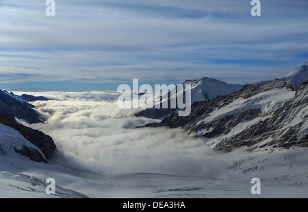 Snow covered peaks poking out above the clouds. It is raining below. Taken at 3500 m above sea level - Stock Photo