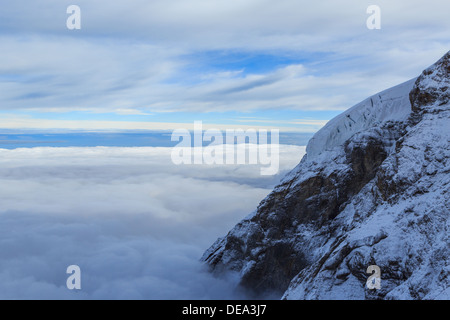 A snow covered peak poking out above the clouds. It is raining below. Taken at 3500 m above sea level - Stock Photo