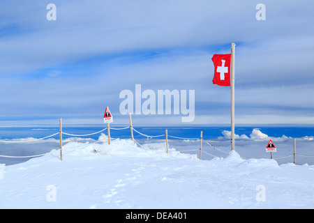 A photograph of a Swiss flag in the Jungfrau region of Switzerland. The peaks are above the clouds and it is raining - Stock Photo