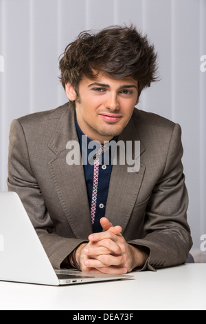 Portrait of successful handsome young manager looking at the camera and smiling confidently in his office. Business - Stock Photo