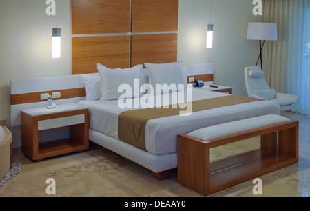 Bedroom interior in a house or hotel with minimalist decor in neutral tones and a large double bed - Stock Photo