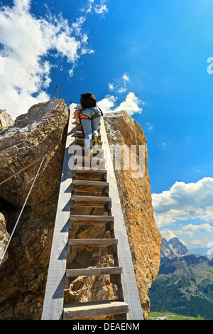 hiker on a big wooden ladder in Bepi Zac via ferrata, Trentino, Italy - Stock Photo