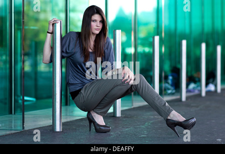 Young woman with high heels posing in front of a green glass wall - Stock Photo
