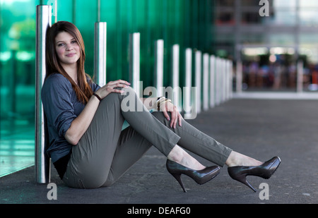 Smiling young woman with high heels sitting and posing in front of a green glass wall - Stock Photo