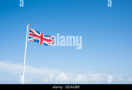 Union Jack flag against blue sky. - Stock Photo