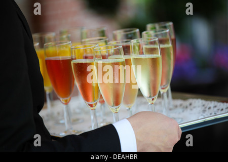 Tray of colorful glasses filled with Champagne - Stock Photo