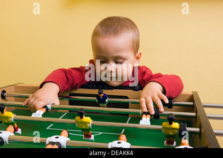 Boy, 2 years, playing with tabletop soccer - Stock Photo