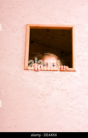 Girl, 3 years, looking through window - Stock Photo