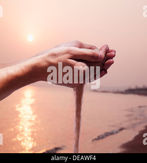 Hands holding and spilling sand with beach at sunset in the background - Stock Photo