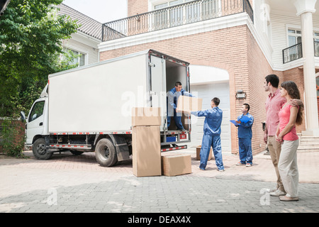Young couple watching movers move boxes from the moving van - Stock Photo