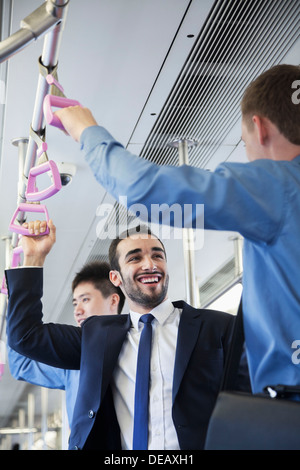 Two businessmen standing and talking on the subway - Stock Photo