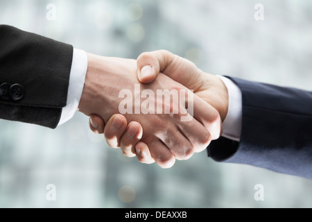 Close-up of two businessmen shaking hands - Stock Photo