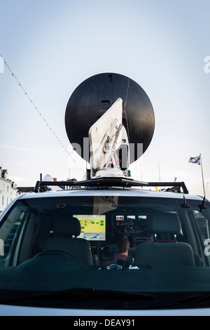 An engineer working in the transmission satellite truck for BBC Wales television news crew doing a live outside - Stock Photo
